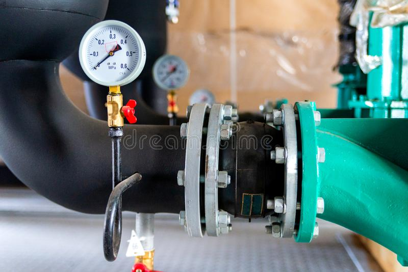 System von Warmwasserleitungen mit Manometer im Heizraum lizenzfreies stockbild