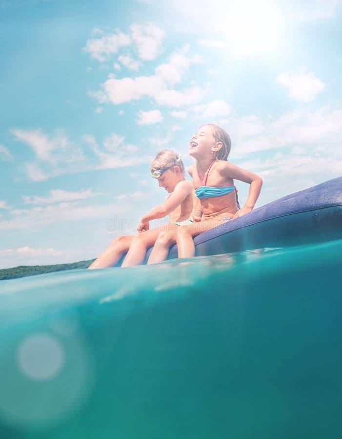 Syster och broder som sitter p? den uppbl?sbara madrassen och tycker om havsvattnet som skrattar glatt n?r bad i havet of?rsiktig royaltyfri foto
