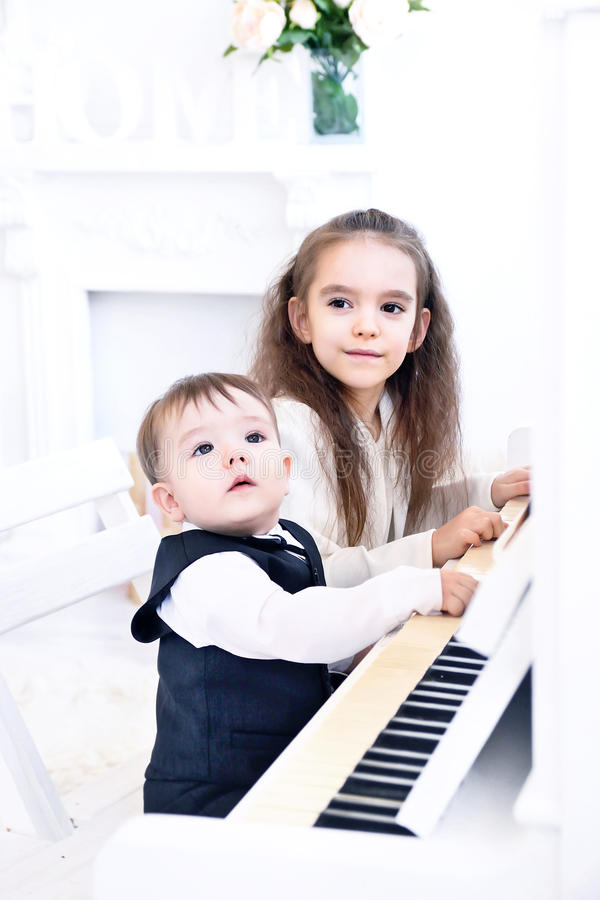 Syster och yngre bror som spelar pianot royaltyfria bilder