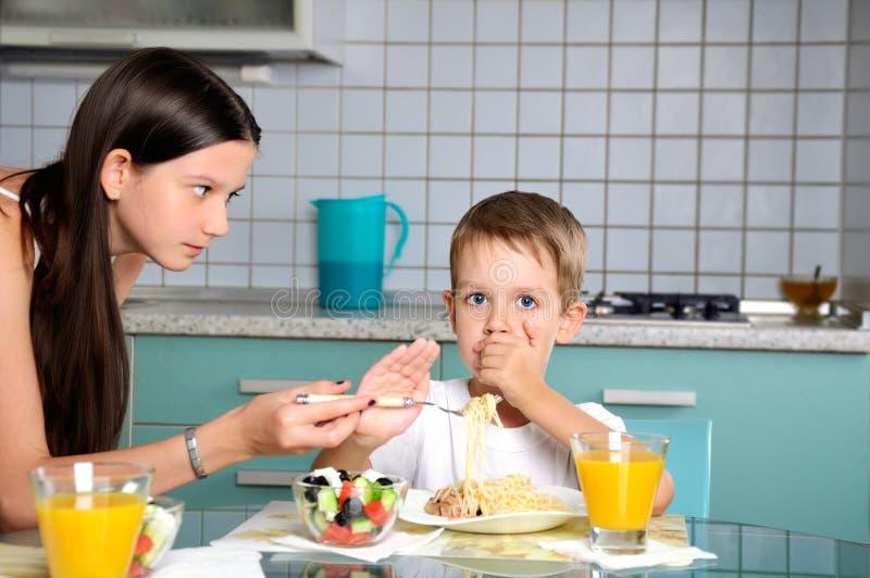Syster som försöker att mata hennes broder han motstår och royaltyfria bilder