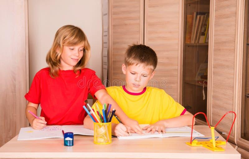 Syster som hjälper hennes broder med hem- uppgift stående två royaltyfri bild