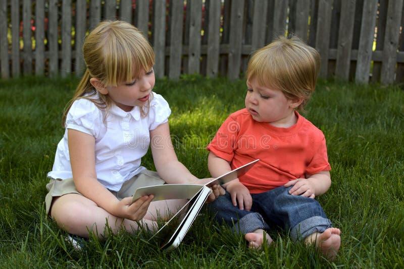 Syster som läser till brodern royaltyfri fotografi