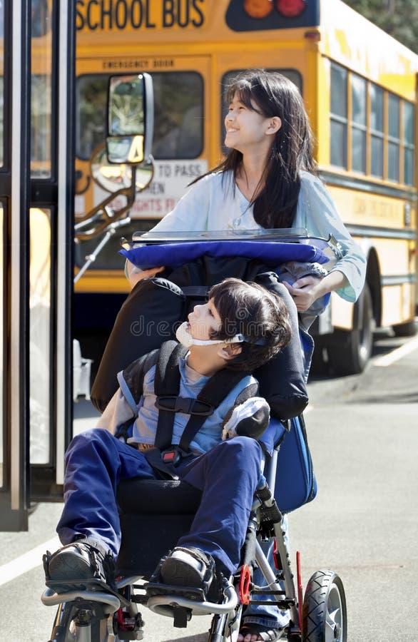Syster som skjuter den inaktiverade brodern i rullstol arkivbild