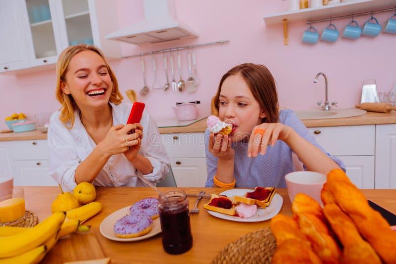 Syster som skrattar, medan filma hennes sibling som äter för mycket sötsaker royaltyfria bilder