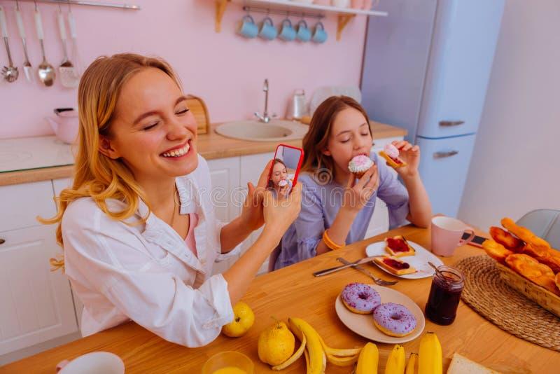 Syster som skrattar stund som gör fotoet av sibling som äter munken royaltyfri foto