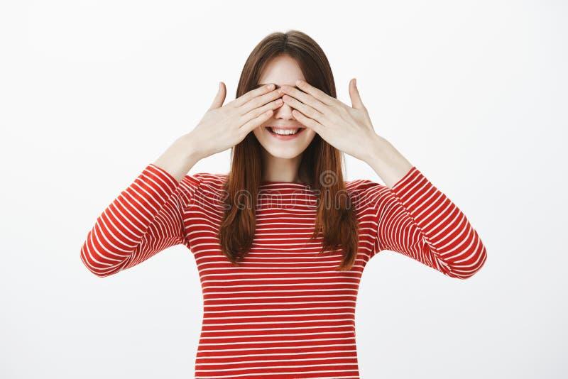 Syster som spelar kurragömma med tonåringar, stängande ögon och att räkna Glad lycklig ung kvinna med brunt hår royaltyfria foton