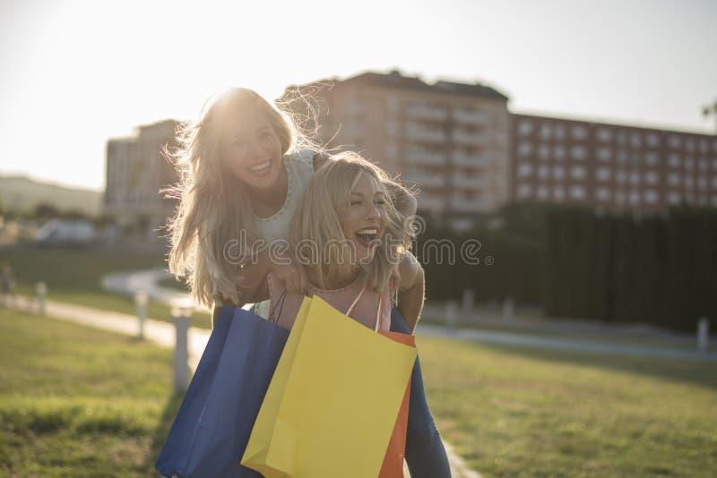 Syster som två spelar på ridtur på axlarna, når att ha shoppat i solnedgångbild royaltyfri foto