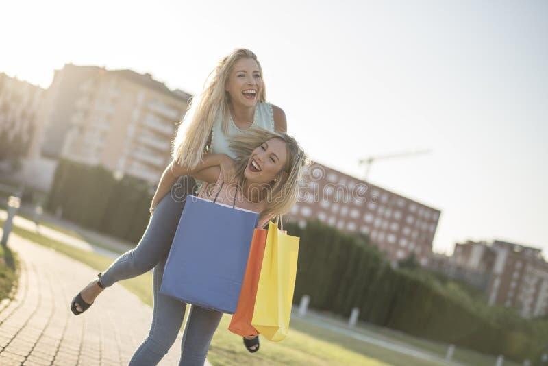 Syster som två spelar på ridtur på axlarna, når att ha shoppat i solnedgångbild arkivfoton