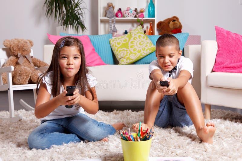 Systern och brodern konkurrerar för hållande ögonen på TV royaltyfria foton
