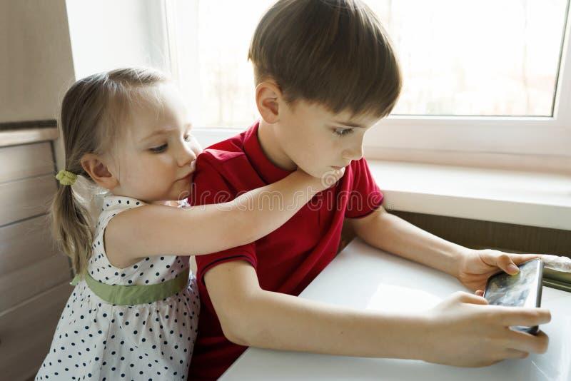 Systern och brodern sitter i k?ket och spelar med telefonen royaltyfri fotografi