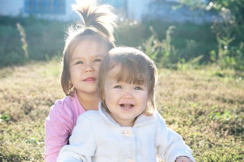 Systerstående utomhus på den soliga dagen lycklig le sibling royaltyfria bilder