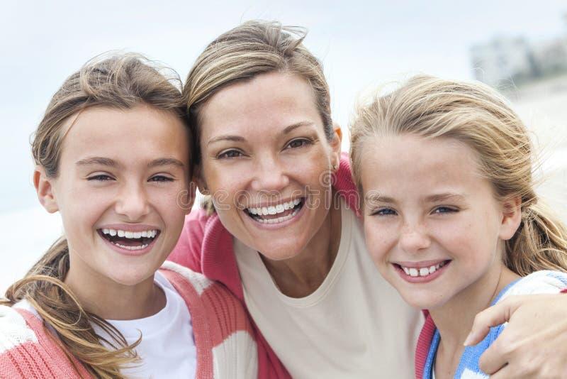 Systrar för kvinnamoder- och flickabarn som är lyckliga på stranden fotografering för bildbyråer