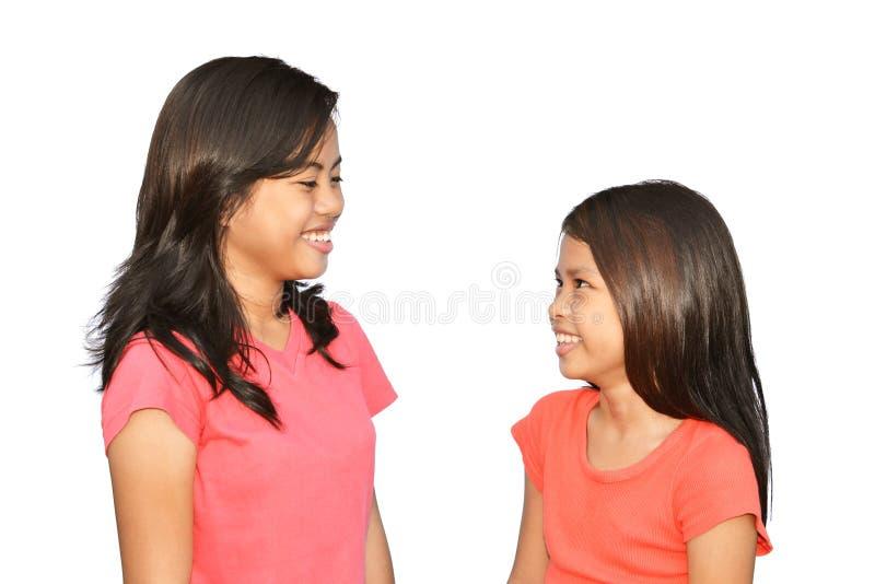 Systrar finner det som är roligt! arkivfoto