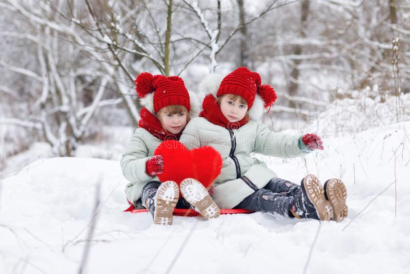 Systrar kopplar samman med hjärta i händerna sitter på den snöig jordningen royaltyfria foton