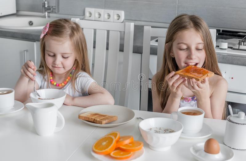 Systrar som äter frunch, havre och rostat bröd med honung royaltyfri bild