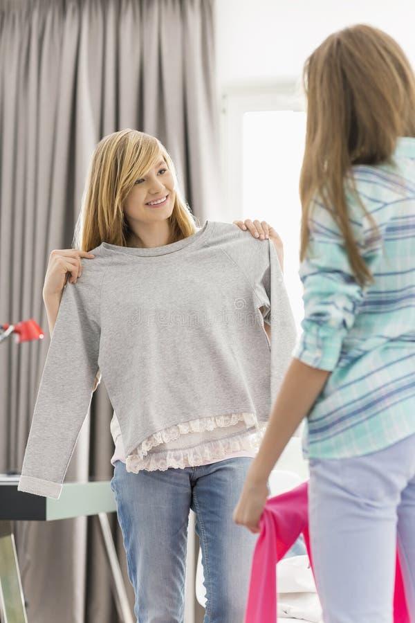 Systrar som hemma försöker på kläder arkivfoton