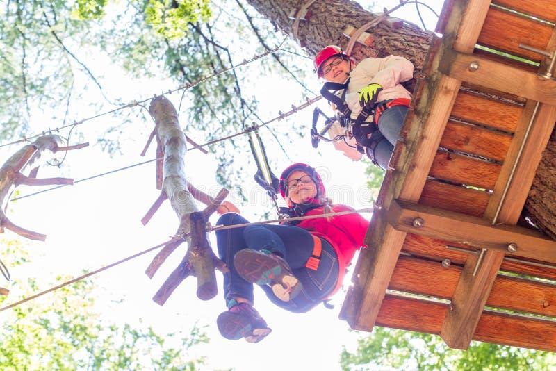 Systrar som klättrar i högt rep, jagar tillsammans royaltyfri foto