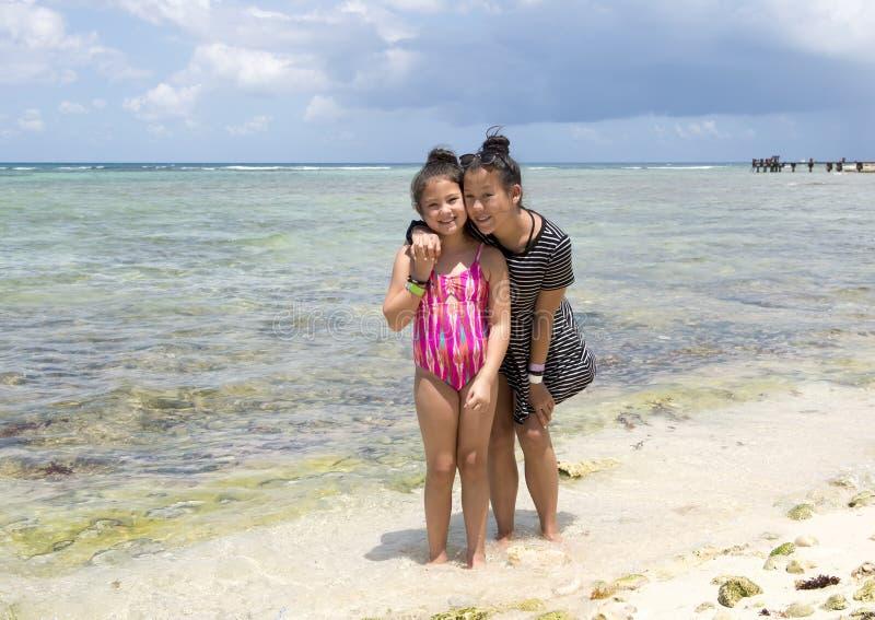 Systrar som poserar på stranden, Half Moon Bay, norr Akumal, Mexico royaltyfri foto