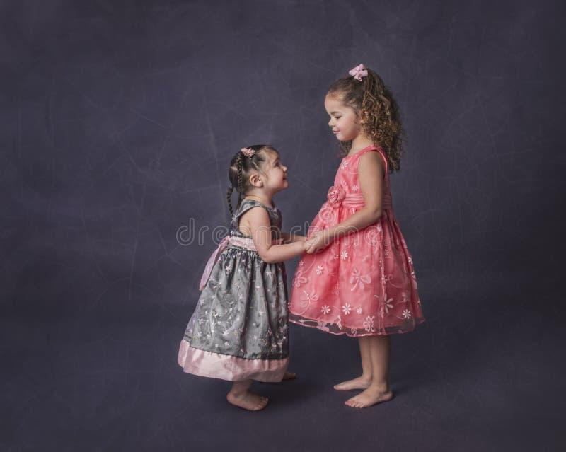 Systrar som rymmer händer på purpurfärgad bakgrund royaltyfri foto