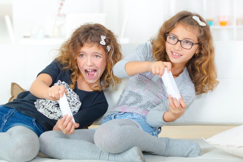 Systrar som spelar på lekkonsolen royaltyfri foto