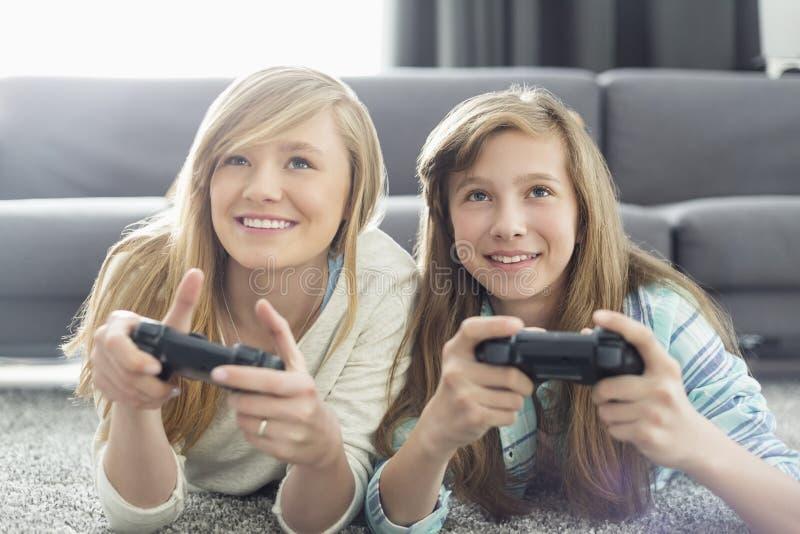 Systrar som spelar videospel i vardagsrum royaltyfri bild