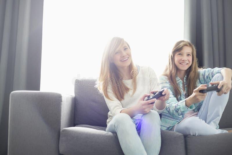 Systrar som spelar videospel på soffan royaltyfria foton