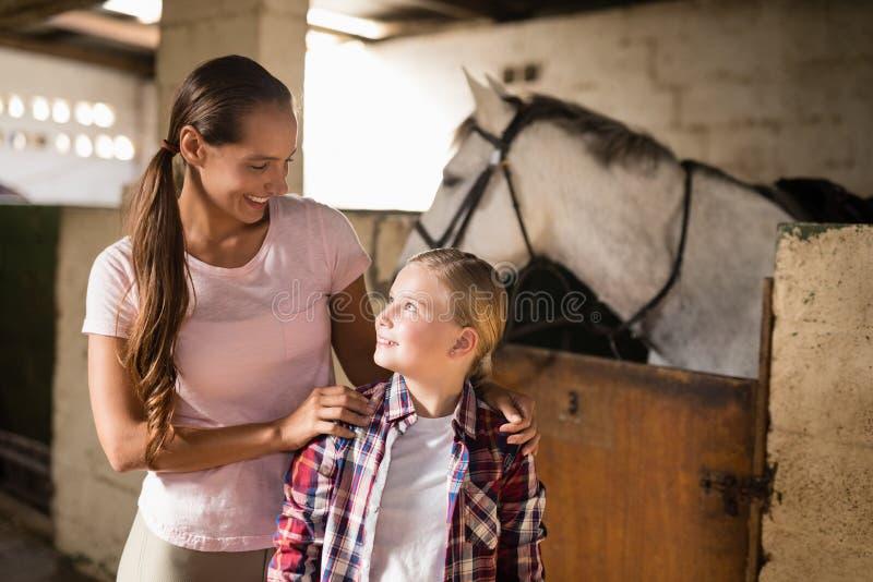 Systrar som talar, medan stå mot häst royaltyfria foton
