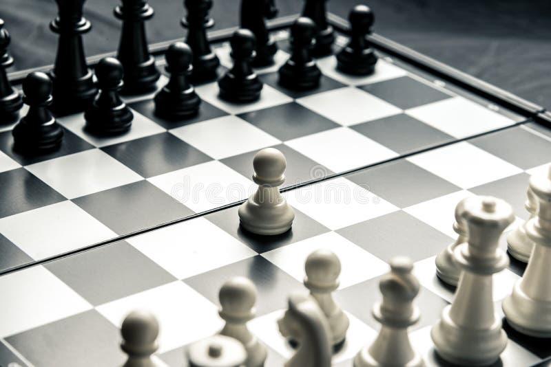 Szachowa deska z czarny i biały szachowym obszyciem each inny Biały pionek iść na ataku zdjęcie royalty free