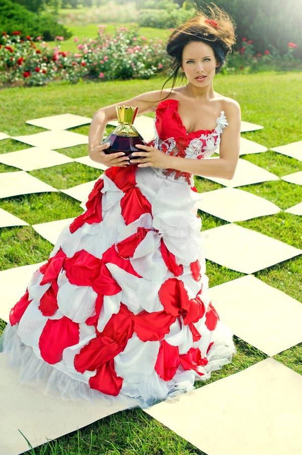 Szachowa królowa trzyma wielką butelkę pachnidło obraz stock