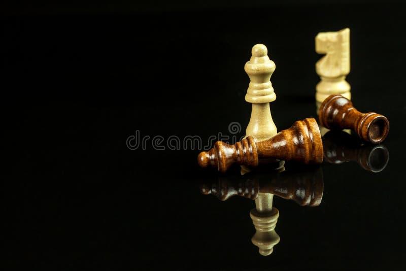 Szachowi kawałki na czarnym tle Sztuka szachy checkmate Pojęcie porażka i zwycięstwo zdjęcie royalty free