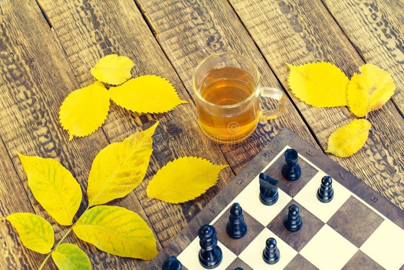 Szachowi kawałki na pokładzie, filiżanka herbata i jesień żółci liście, obrazy royalty free