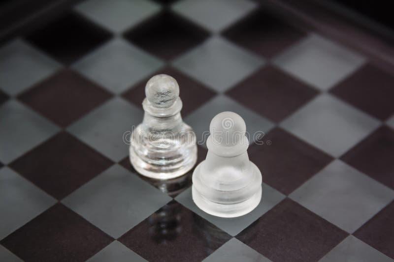 Szachowi kawałki robić szkło: konfrontacja między dwa pionkami przeciw czarnemu tłu zdjęcia stock