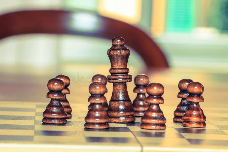Szachowi pionkowie wokoło szachowego królewiątka na stole Szachowa gra, strategia zdjęcie royalty free