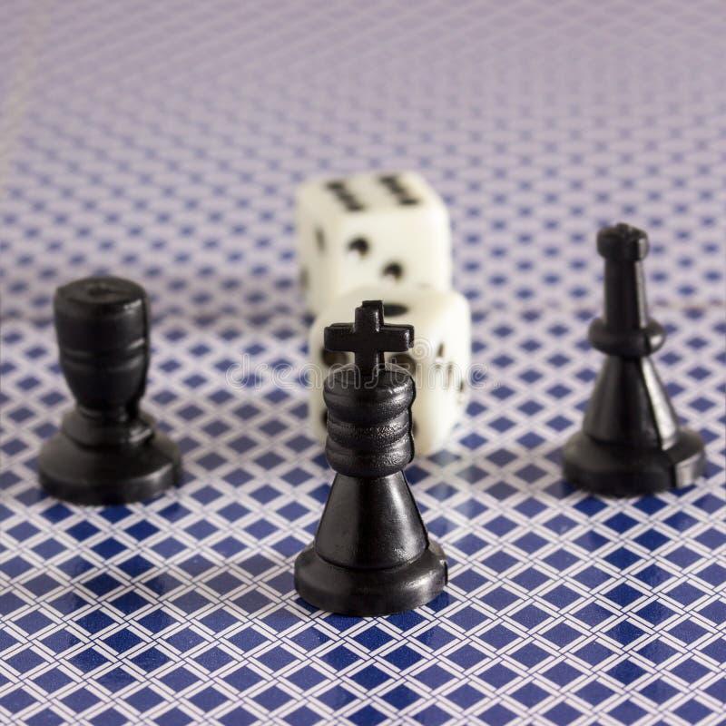 Szachowy królewiątko na zamazanym tle inny postacie i kostka do gry obraz royalty free