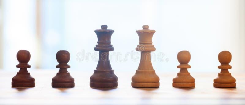 Szachowych kawałków zmrok, jasnobrązowy kolor Zbliżenie widok królowe i pionkowie z szczegółami Plamy tło zdjęcia royalty free