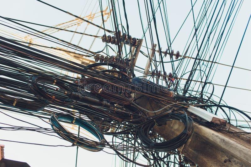 Szaleni upaćkani chaosów drutów kable na Elektrycznych słupach fotografia stock