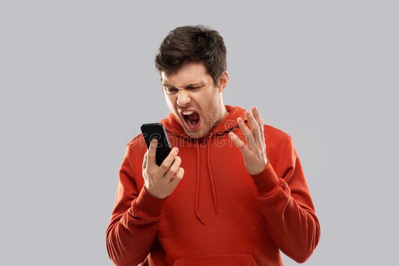 Szalenie mężczyzna krzyczy smartphone w czerwonym hoodie obraz royalty free