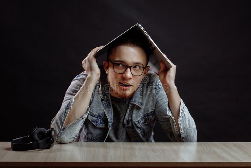 Szalenie mężczyzna stawia na laptopie na jego głowie rof od notatnika obrazy stock