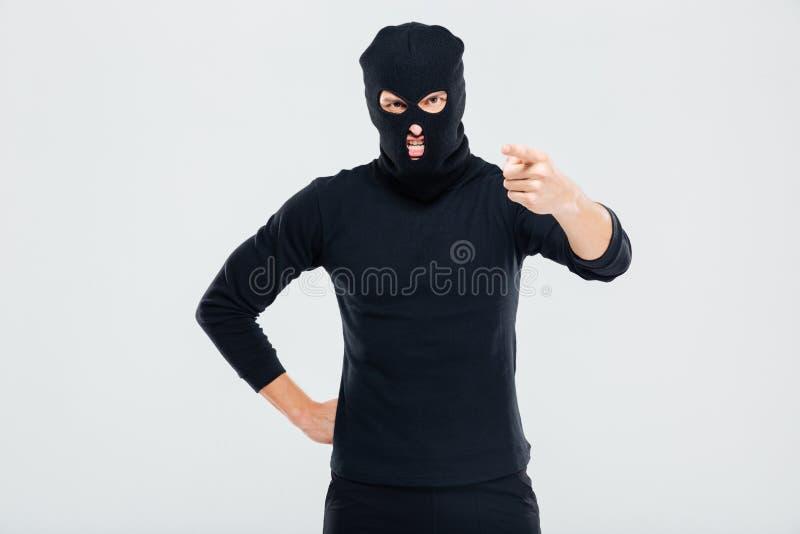 Szalenie podrażniony mężczyzna w balaclava wskazywać na tobie i pozyci obrazy royalty free