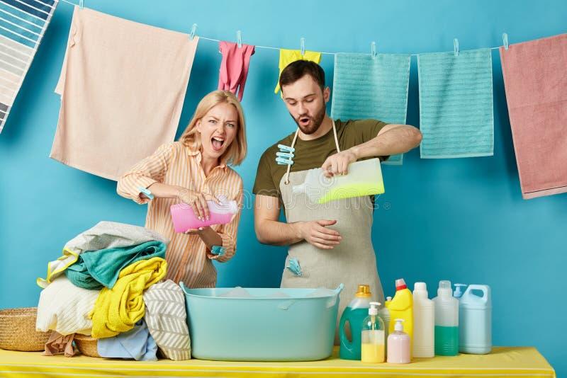Szalona śmieszna para nalewa różnych detergenty w pucharze fotografia royalty free