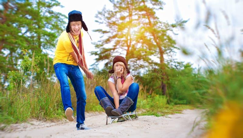 Szalona chłopiec i dziewczyna sledding przy latem zdjęcie royalty free