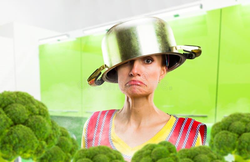 Szalona gospodyni domowa w fartuchu z garnkiem na jej głowie zdjęcie royalty free