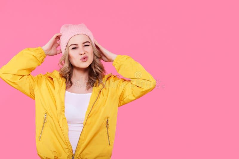 Szalona piękna modna dziewczyna w jaskrawych żółtej kurtki i menchii beanie kapeluszu puckering wargach Chłodno młodej kobiety mo obraz stock