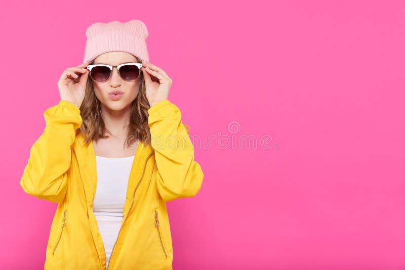 Szalona piękna modna dziewczyna w kolorowych ubraniach, różowego beanie puckering wargach i trzymać okularach przeciwsłonecznych  obraz royalty free