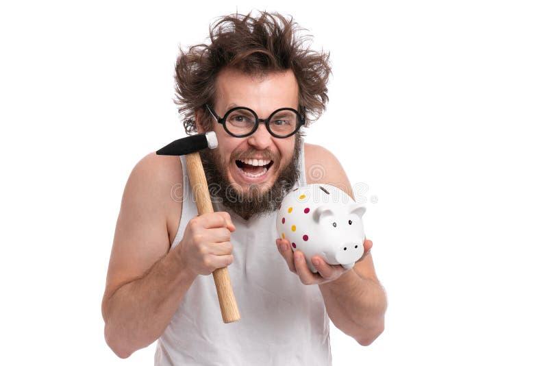 Szalony brodaty mężczyzna z prosiątko bankiem fotografia royalty free