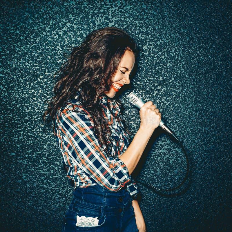 Szalony dziewczyny mienia mikrofon i ono uśmiecha się Atrakcyjny Piękny zdjęcie royalty free