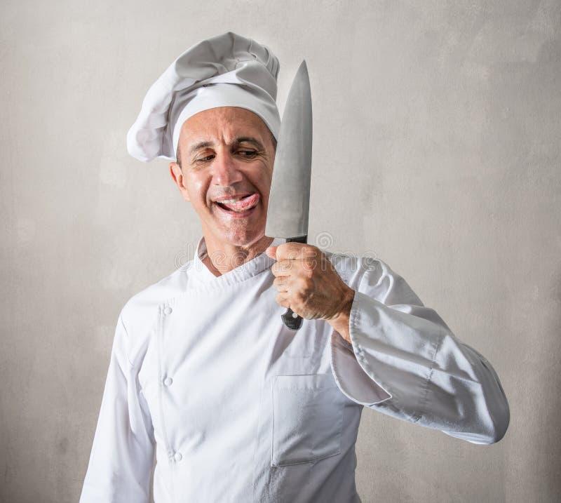 Szalony kucharz liże nóż zdjęcia royalty free