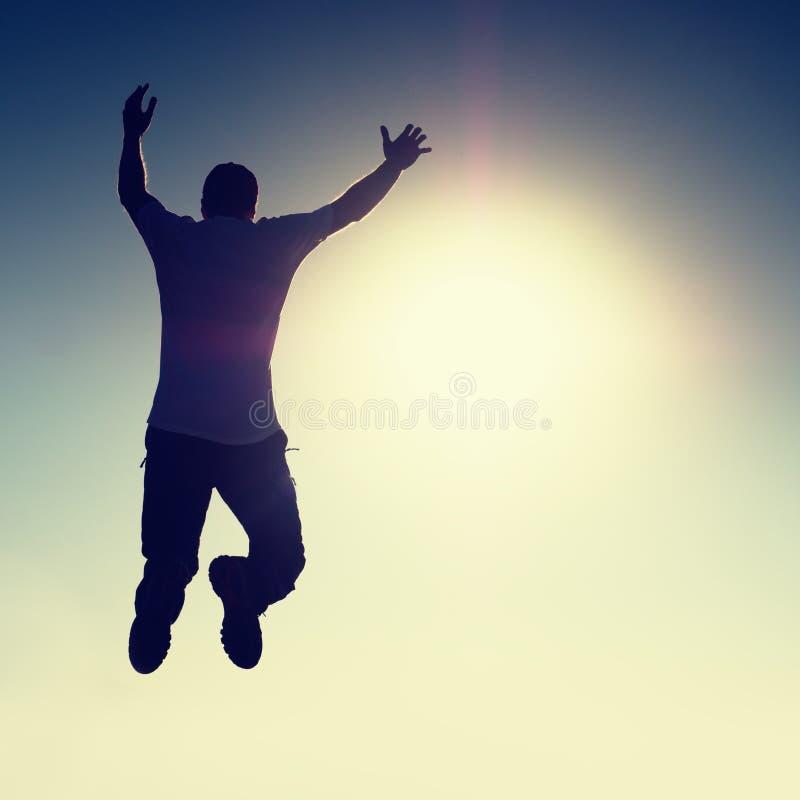 Szalony mężczyzna lata nad słońcem na niebieskiego nieba tle obrazy stock