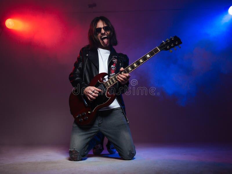 Szalony młody gitarzysta bawić się gitarę elektryczną i shoing jęzor zdjęcia royalty free