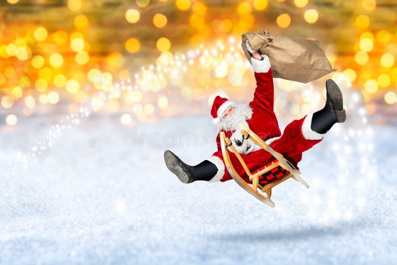 Szalony Santa Claus latanie na jego sania bokeh śnieżnym złotym backgro zdjęcie stock